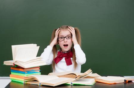 reading glasses: Shocked teen girl near empty green chalkboard.
