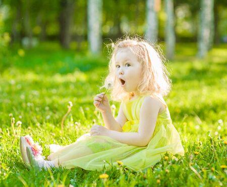 blowing dandelion: little girl blowing dandelion. Stock Photo
