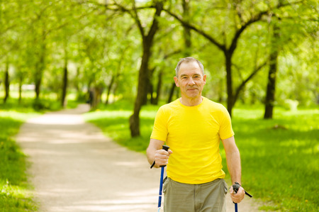 Happy elderly people engaged in Nordic walking. Banque d'images