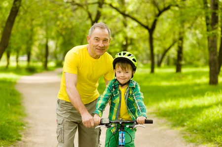 An old man teaching his grandson to ride a bike. Stock Photo