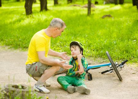 child sport: Grandpa calms grandson that fell from the bike.