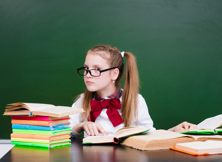 specs: Young girl reading a book near empty green chalkboard.