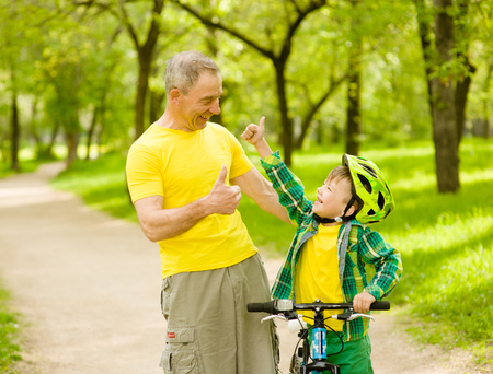 grandson and grandfather having fun riding a bike.