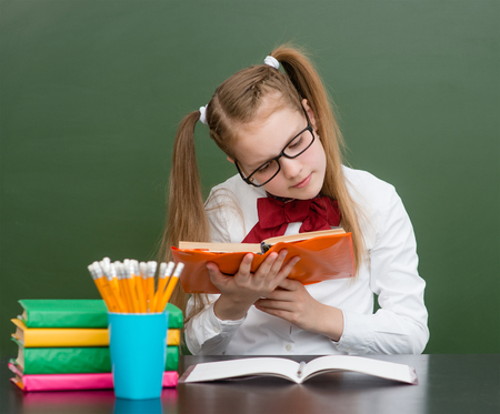 Girl with poor eyesight reading a book. Stock Photo