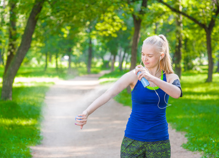 Woman spraying insect repellents on skin before run.