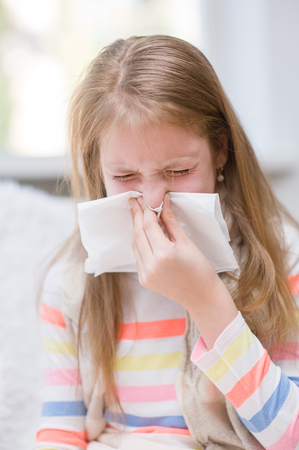 rheum: Young girl blowing her nose.