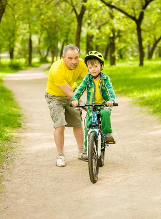 teaches: Grandfather teaches his grandson to ride a bike. Stock Photo