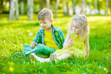 Little girl and boy sitting together on green grass.