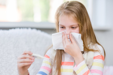 Young girl blowing her nose and checks the temperature.
