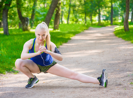 Young fitness woman runner stretching legs before run. Banque d'images