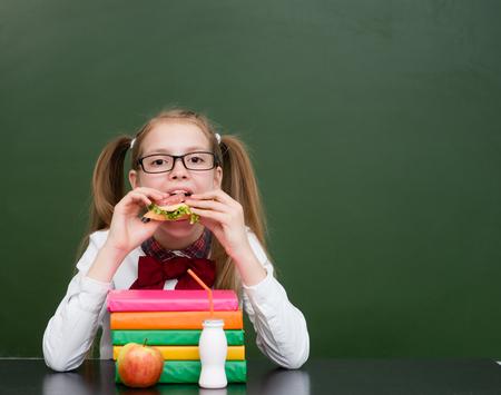 niños comiendo: niña de la escuela que come el emparedado cerca de pizarra verde vacía.