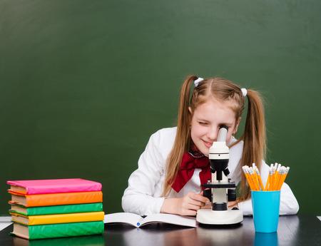 science class: Girl examining preparation under the microscope. Stock Photo