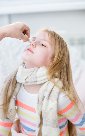 medicate: mother medication drips into the nose girl. Stock Photo