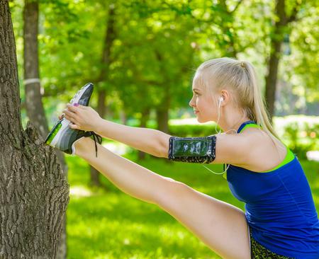 piernas mujer: Joven corredor de la mujer de la aptitud que estira las piernas antes de correr. Foto de archivo
