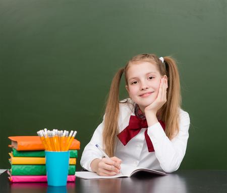Happy teen girl sitting in classroom near empty green chalkboard.