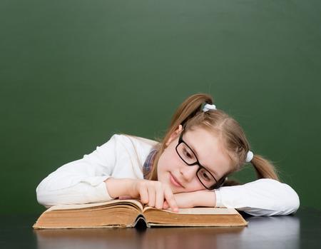 poor eyesight: Girl with poor eyesight reading a book. Stock Photo