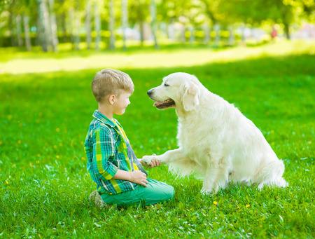 obediencia: Niño jugando con el perro en la hierba verde.