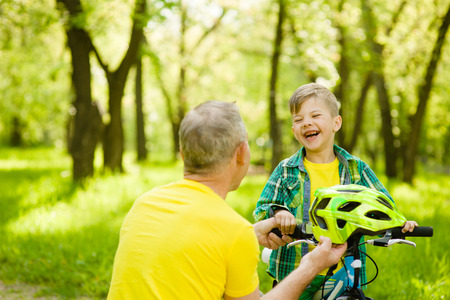grandson: Grandfather gives his grandson a bicycle helmet. Stock Photo