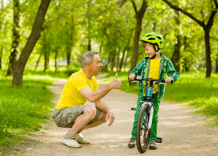 old man happy: Father talking with his son riding a bicycle and showing thumbs up. Stock Photo
