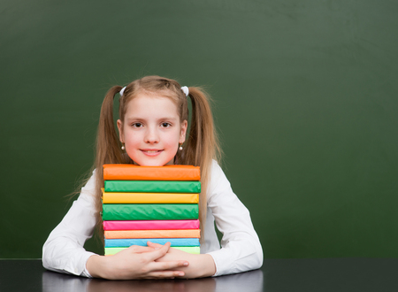 pile of books: Happy girl hugs pile books near empty green chalkboard.