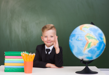 knowing: Young boy in a business suit raising hand knowing the answer to the question.