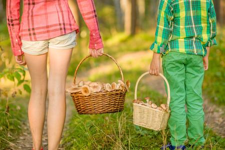 Boy and girl carry a baskets with mushrooms.