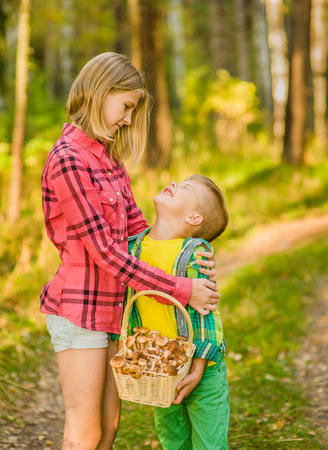 Sister calms a boy lost in the woods. Stock Photo