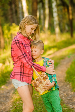 astray: Sister calms a boy lost in the woods. Stock Photo