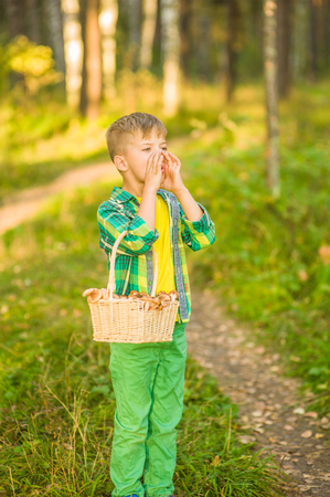 Boy shouting out loud in the forest with hands cupped around mouth.