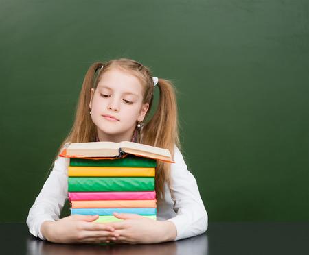 pile of books: Schoolgirl with pile books near empty green chalkboard.