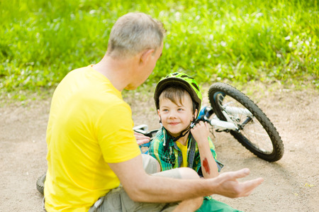 fell: Grandpa calms grandson that fell from the bike.
