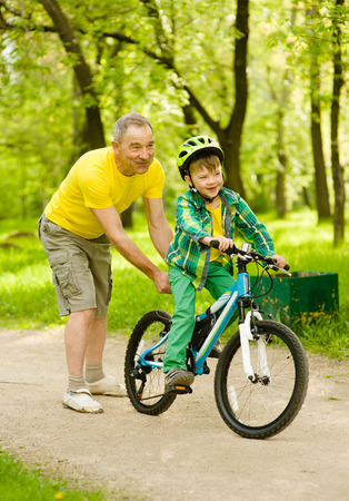 dad son: Father teaches his son to ride a bike.