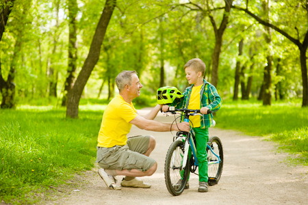 Grandfather gives his grandson a bicycle helmet. Stock Photo