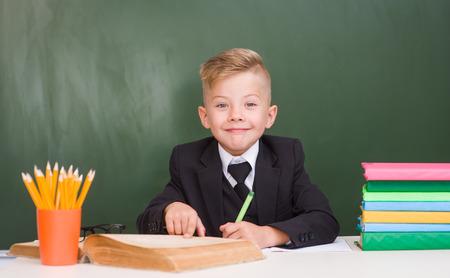 schoolboy: Happy schoolboy in a suit in classroom. Stock Photo