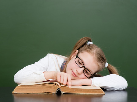 poor eyesight: Girl with poor eyesight reading a book. Stock Photo