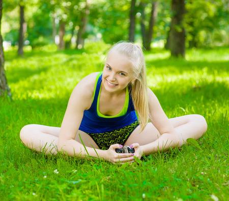 donna farfalla: Felice fitness donna farfalla si estende gambe nel parco estivo all'aperto.