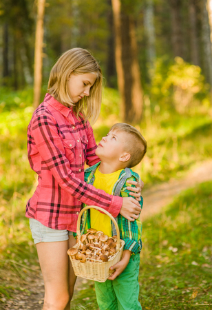 Sister hugging brother in the forest.