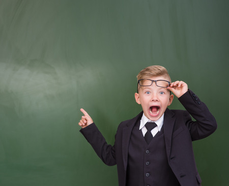 Surprised boy stands near empty chalkboard and showing finger up. Stock Photo