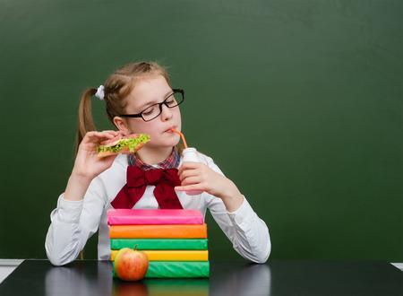 comedor escolar: leche de la bebida de la chica joven en el aula. Foto de archivo