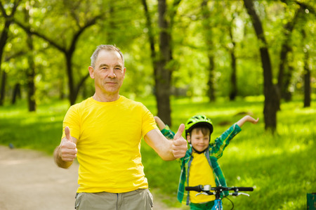 old man happy: Father and son on a bicycle in the park. Stock Photo