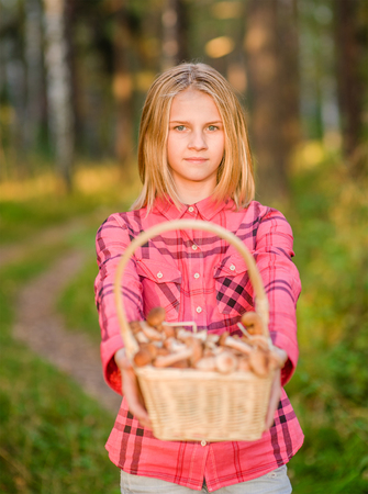 Girl holding a basket of mushrooms in autumn forest.
