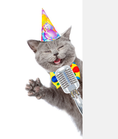 Cat in birthday hat holds retro microphone. isolated on white background Stock Photo
