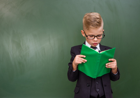 schoolboy: Schoolboy with book near empty green chalkboard.
