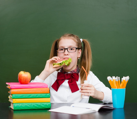 School girl eating sandwich near empty green chalkboard.