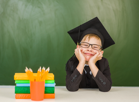 Happy boy in graduation cap looking at camera near empty green chalkboard. Stock Photo
