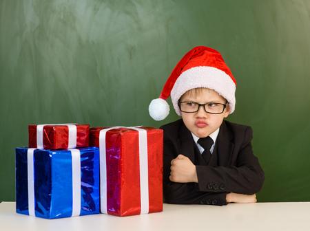 Funny boy in Santa red hat near gifts.