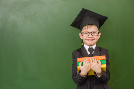 Boy in graduation cap with books standing near green chalkboard.