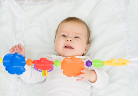 attention grabbing: Happy newborn baby girl playing with toy rattle lying on back. Stock Photo