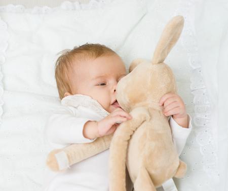 bébé nouveau-né Bonne joue avec le jouet de lapin.