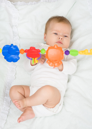 attention grabbing: Newborn baby girl playing with toy rattle lying on back.